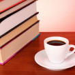 Books pile and cup of coffee on the table and red background — Stock Photo