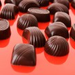 Assorted chocolate candies on red background — Stock Photo