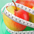 Stock Photo: White tape measure around red apple representing dieting