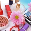 Many colourful woman cosmetics with flower on white white back — Stock Photo #6679551