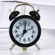 Black alarm clock and documents — Stock Photo #6679639