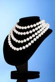 Collana di perle su un manichino su sfondo blu — Foto Stock