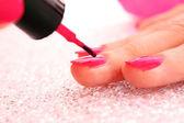Woman applying pink nail polish — Stock Photo