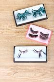 Beautiful decorative eyelashes on wooden background — Stock Photo