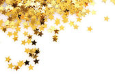 Golden stars in the form of confetti on white — Stok fotoğraf