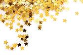 Gouden sterren in de vorm van confetti op wit — Stockfoto