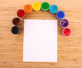 Opened paint buckets colors and paper on the table — Stock Photo