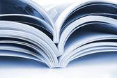 Pile of open magazines isolated on white background — Stock Photo