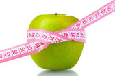 Zelené jablko a měřicí pásky — Stock fotografie