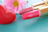 Two new lipsticks and pink flower on blue background — Stock Photo