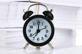 Black alarm clock and documents — Stock Photo