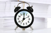 Black alarm clock and documents — Stock Photo