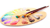 Wooden art palette with blobs of paint and a brush on white back — Stock Photo