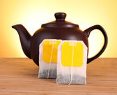 Close-up of tea bag and teapot on yellow background — Stock Photo
