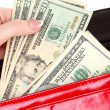 Stock Photo: Red purse with dollars in the hands on a white background