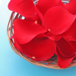 Royalty-Free Stock Photo: Basket with red roses petals on blue
