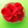 Stock Photo: Basket with red roses petals on green