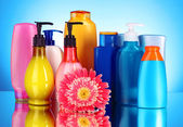 Bottles of health and beauty products on blue background with re — Stock Photo