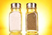 Glas salt- och pepparkar på gul bakgrund — Stockfoto