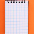 Notebook  on the orange background - Stock Photo