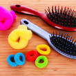 Hair Brush and hair scrunchies on brown background — Stock Photo