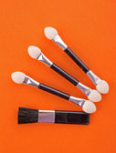 Cosmetic brushes on orange background — Stock Photo
