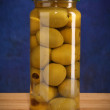 Royalty-Free Stock Photo: Pickled olives in glass jar on blue
