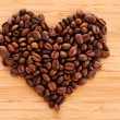 Coffee beans in heart shape on brown background - Zdjcie stockowe