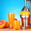 Juicer and oranges on blue background - Stock Photo