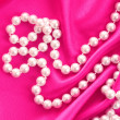 Smooth elegant red silk background with pearls — Stock Photo #6711889