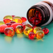 Red capsules of vitamins on a blue background — Stock Photo #6712685