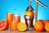 Juicer and oranges on blue background — Stock Photo