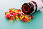Red capsules of vitamins on a blue background — Stock Photo