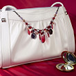 White handbag with necklace and small mirror — Stock Photo