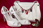 White high-heeled shoes and handbag with necklace — Stock Photo