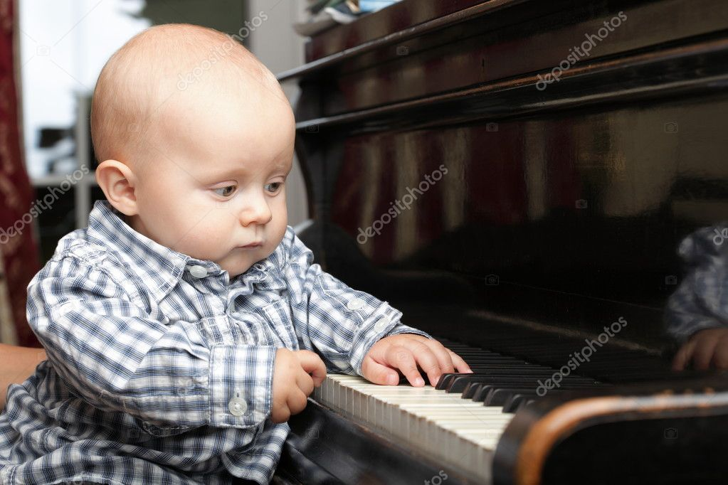 Beautiful little baby boy learning plays piano — Stock Photo #6743120