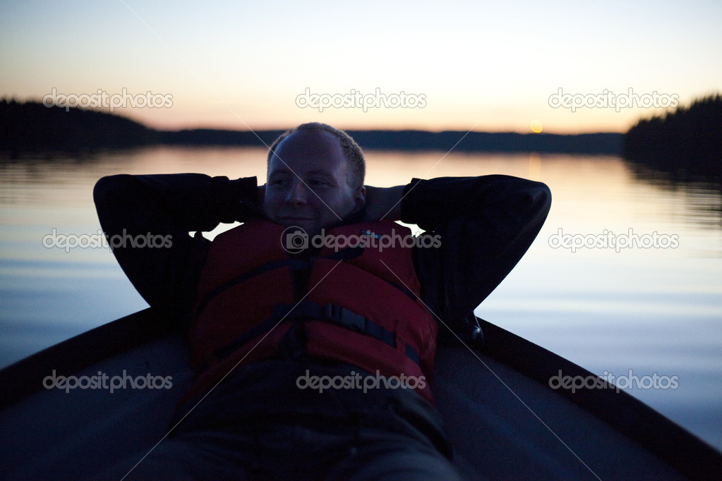 Young man relaxing on the boat just after sunset  Stock Photo #6721705