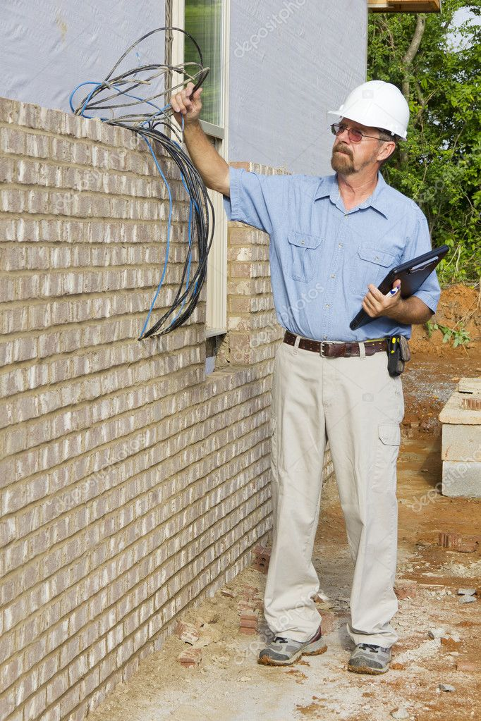 Building inspector checking electrical wires,phone lines, building framing,electrical and plumbing stub outs — Stock Photo #6737606