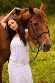 Mladá krásná žena s koněm