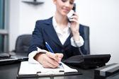 Podnikatelka psaní schůzky a pomocí telefonu