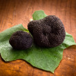 thumbnail of Black truffle over leaf on wood background