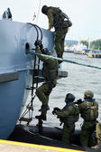 Soldiers marines ( sea commandos ) boarding a ship in a simulated assault.