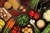 Foto di un tavolo pieno di verdure fresche, frutta e altri alimenti sani