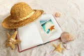 Book with straw hat and seashells in sand