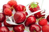 Třešně a jahody v lžíci izolované na bílém
