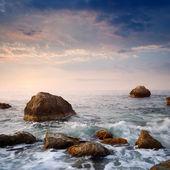 Sunrise on rocky sea coast