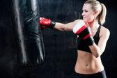 Boxing training woman punching bag in gym