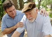Uomo anziano in mancanza di salute e suo figlio preoccupato di mezza età. concentrarsi sulluomo anziano