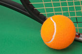 tenisovou raketu a míček na zeleném pozadí