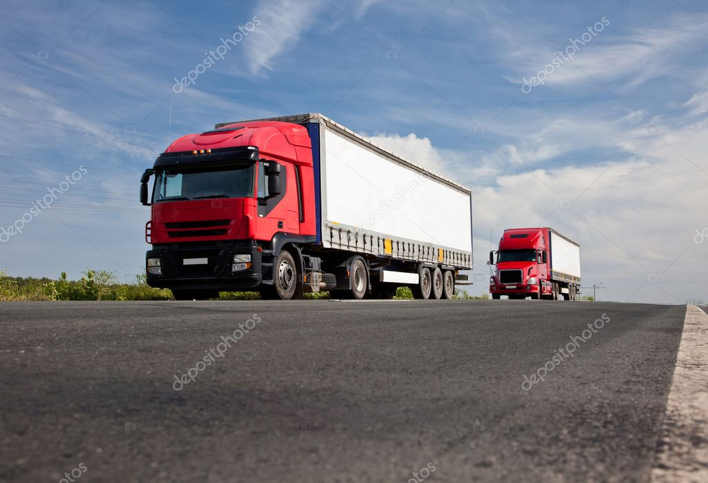 Two red trucks on road